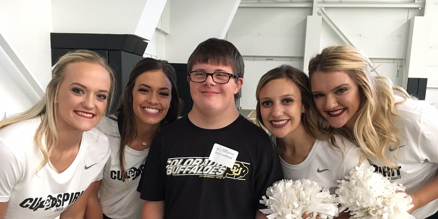 Smiling man with a developmental disability, Jess Lawhead, wearing a CU Buffaloes shirt surrounded by cheerleaders for the CU Buffeloes