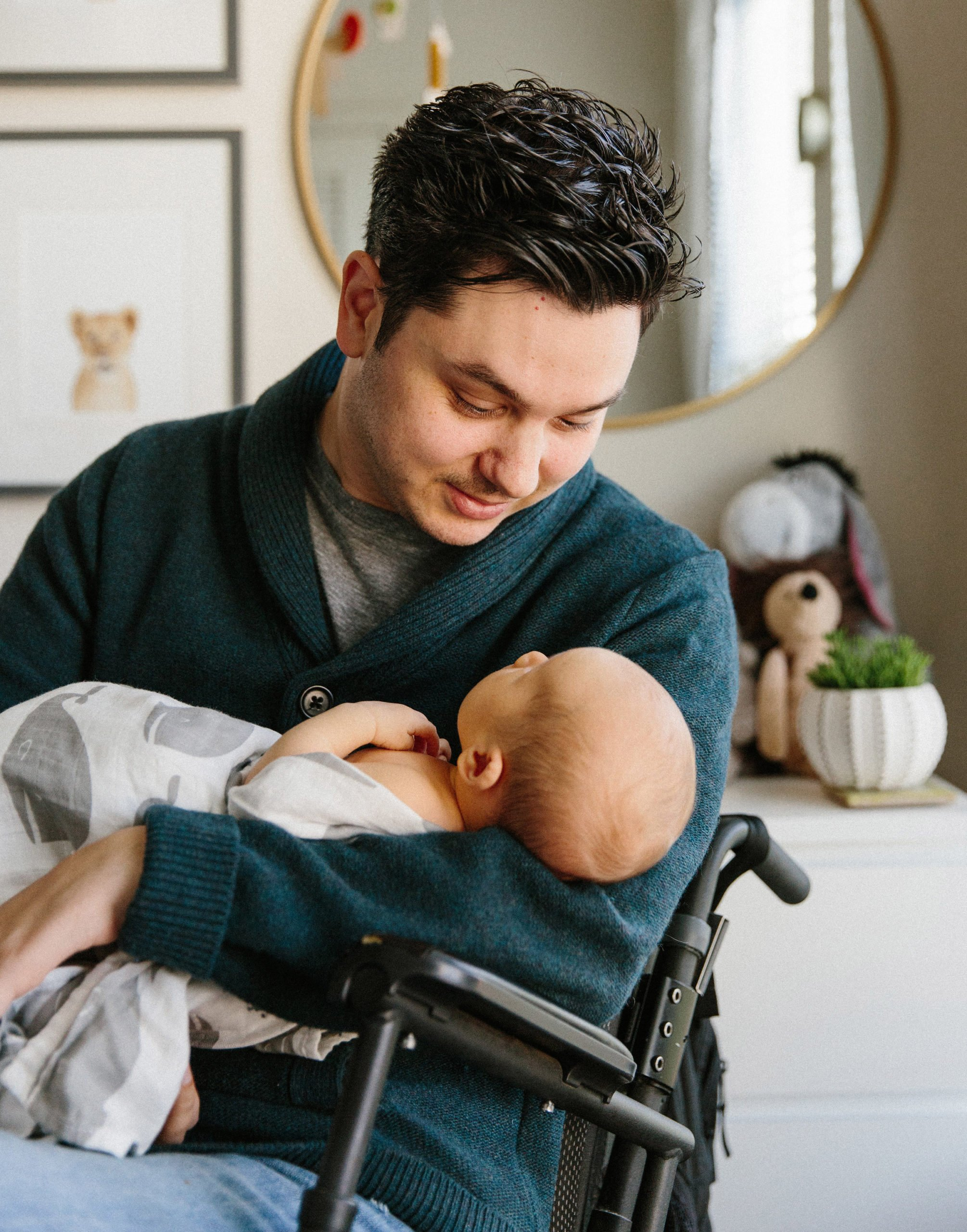 Man in wheelchair, Zack Weinstein, cradles his baby son, Theo, in his arms