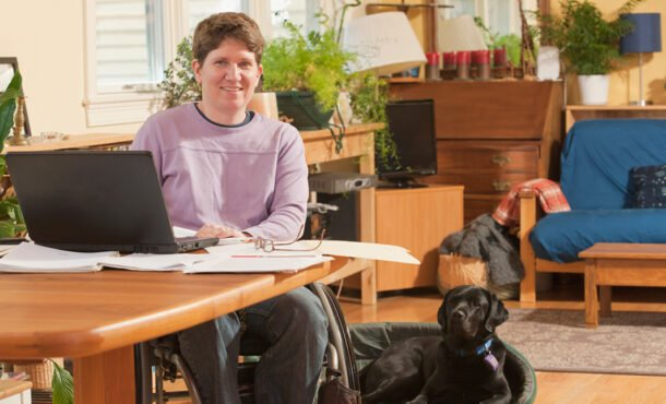 Businesswoman with multiple sclerosis in a wheelchair doing paperwork at home along with her service dog