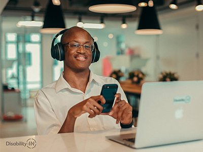 Smiling Black disabled man with glasses and headphones looking at phone with computer in front of him