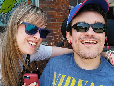A sister and brother wearing sunglasses smiling together. The brother, Robert Zotynia, is a white man who has a developmental disability and is using a wheelchair
