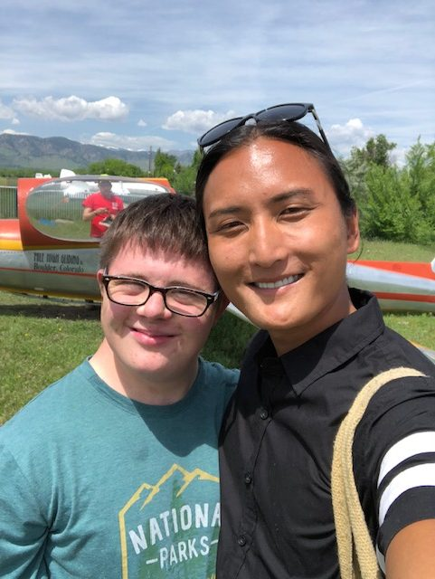 Autistic trans man with friend in front of a small airplane. Both are smiling.