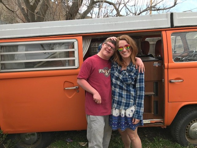 Smiling autistic man, Jess Lawhead, arm-in-arm with female friend wearing rainbow sunglasses in front of an orange van