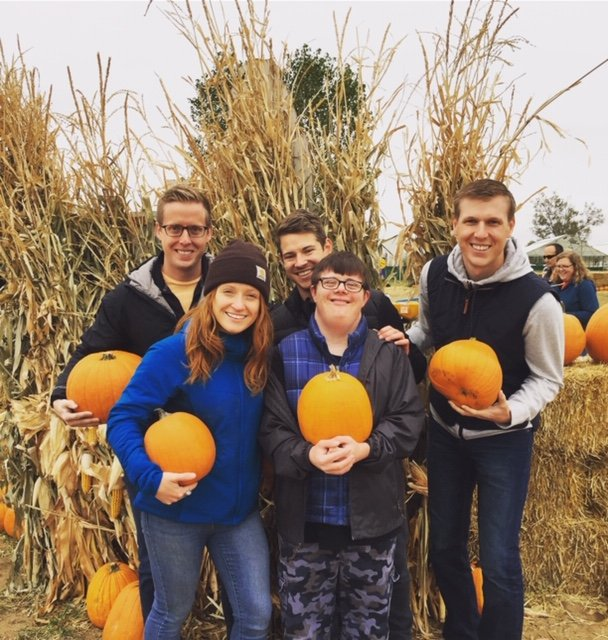 Autistic man Jess Lawhead surrounded by his family all holding pumpkins in a pumpkin patch