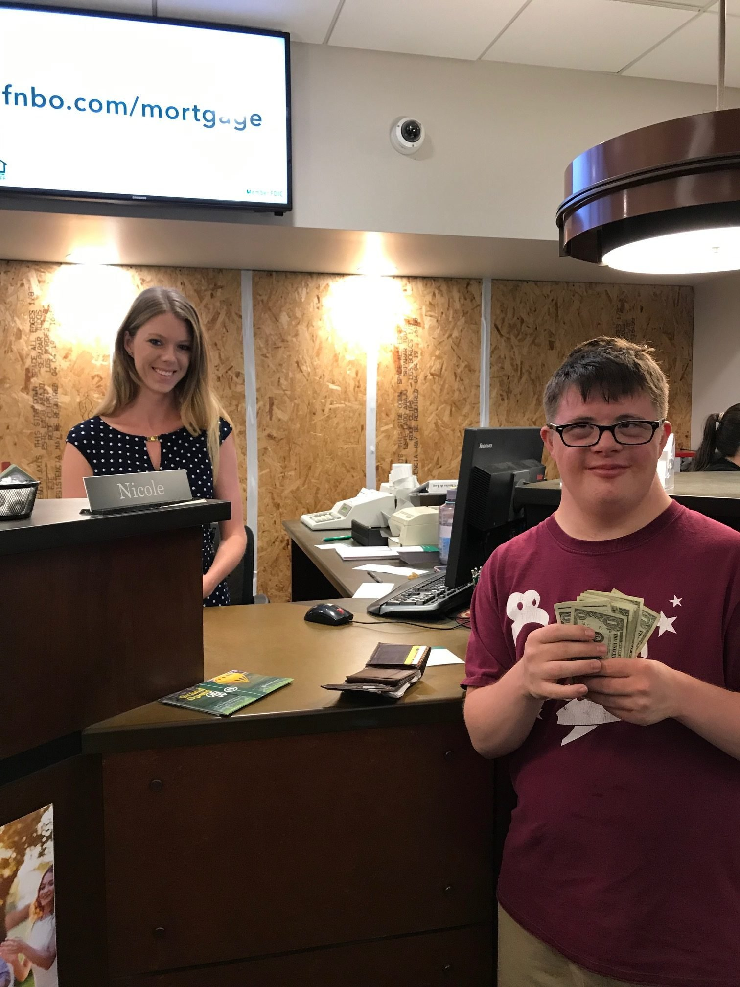 Autistic man Jess Lawhead holding money and smiling in front of a bank teller