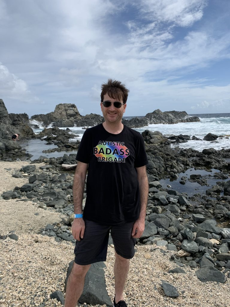 "Jason Ross at beach wearing black shirt saying ""Autistic Badass Brigade"""