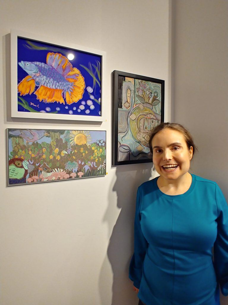 Mara Clawson, smiling disabled white woman wearing a blue dress, stands in front of 3 pieces of their art. The most visible piece is a vibrant betta fish painted blue with yellow/orange fins.
