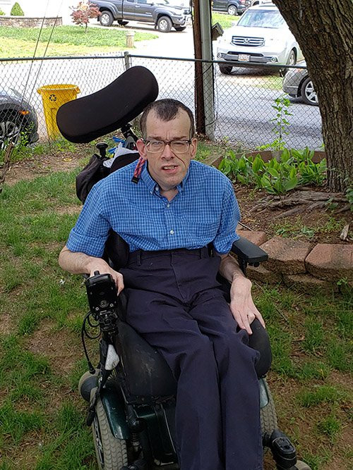 Edward Willard, White man with cerebral palsy in wheelchair. Wearing collared blue checked shirt and navy slacks