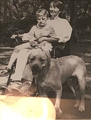White woman in wheelchair with child in her lap and dog next to her
