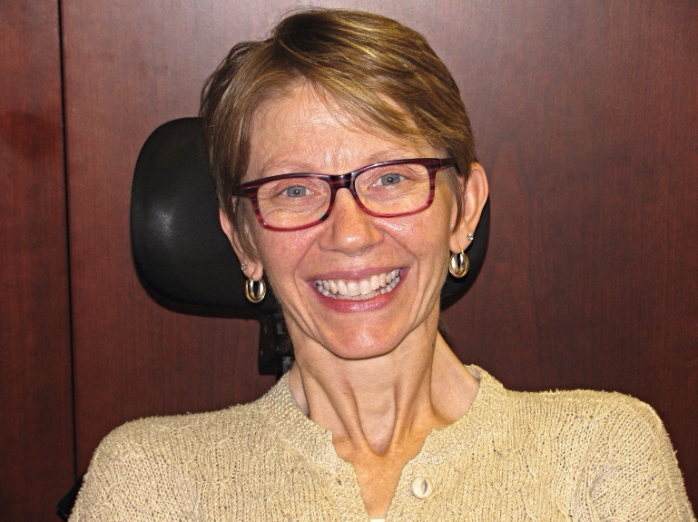 Caroline Signore, White woman in a wheelchair with short brown hair and glasses and a beige sweater