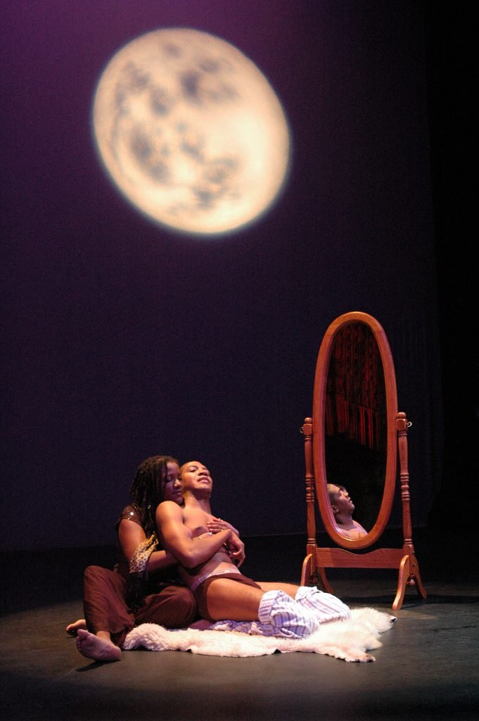 LATEEF MCLEOD AND LISA THOMAS ADEYEMO, ©RICHARD DOWNING 2007 Image Description: Beneath an enormous, bright and shadowy full moon, before a large free-standing mirror with a wooden frame, a Black man lies back in the arms of a Black woman. He wears black underwear, his pants around his knees, sitting on a sheep skin, his arm folded in front of him. She cradles him, her head resting on his shoulder