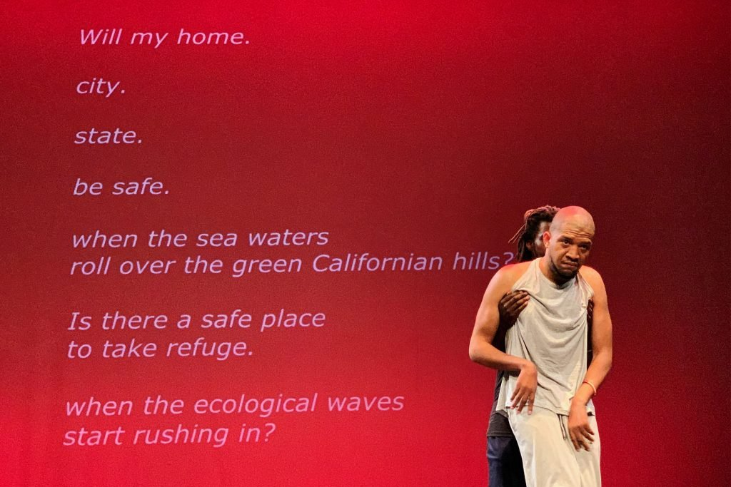 """Lateef McLeod, a Black disabled man with cerebral palsy is held up by another Black man, Sean Shelly, standing behind him. A bright red screen behind them reads """"Will my home. city. state. be safe. when the sea waters roll over the green Californian hills? Is there a safe place to take refuge. When the ecological waves start rushing in?"""" Photo by Richard Downing."""