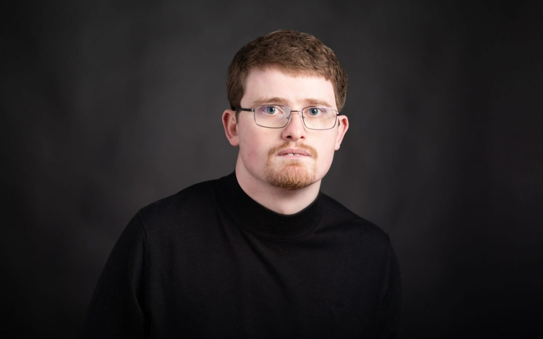 DJ Savarese, white autistic man with glasses and wearing a black turtleneck
