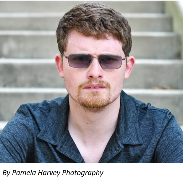 Board member photo of David (DJ) Savarese, white man in blue shirt with sunglasses and facial hair sitting on concrete stairs outside Photo by Pamela Harvey Photography