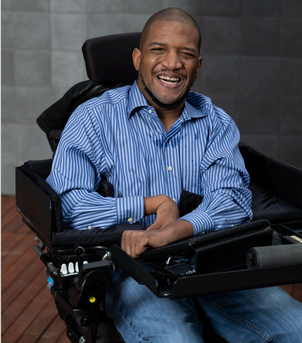 Lateef McLeod, Black man seated in power wheelchair outside on a wood panel floor with a grey wall behind him